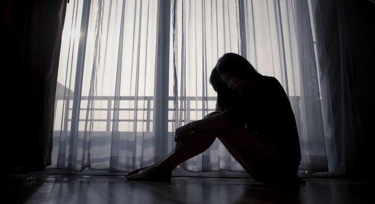 Kvinde der sidder på gulvet